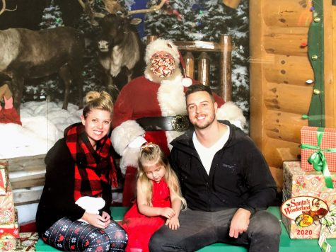Sarah Rhine, her husband Kyle Rhine, and their daughter Emma Rhine got their picture with Santa Claus at Bass Pro Shop.